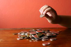 Hand picking a coin from a Bunch of loose change or coins Royalty Free Stock Images