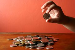 Hand picking a coin from a Bunch of loose change or coins Stock Images