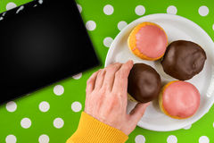 Hand picking donut with sweet chocolate topping from a plate Royalty Free Stock Photo