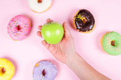 Hand picking fresh green apple surrounded by of tasty donuts. Healthy food concept Royalty Free Stock Images