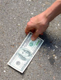 Hand picking money from street floor Royalty Free Stock Photos