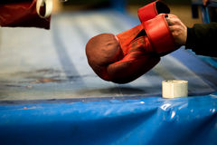 Hand is picking old boxing glove from the ring floor Royalty Free Stock Photography