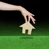 Hand picking paper house over grass field Royalty Free Stock Image