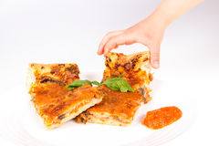 Hand picking a piece of pizza. Childes hand picking a piece of pizza Stock Photos