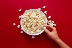 Hand picking popcorn in white bowl royalty free stock image