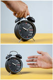 Hand picking up a clock Stock Image