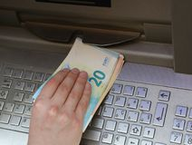 Hand picking up a lot of money from an ATM with euro currency Royalty Free Stock Photo