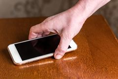 Hand picking up mobile phone from table. stock photos