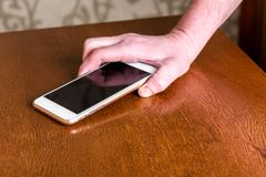 Hand picking up mobile phone from table. royalty free stock images
