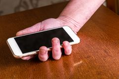 Hand picking up mobile phone from table. royalty free stock photos