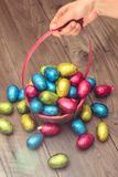 Hand picking up a straw basket filled with Easter chocolate eggs wrapped in colorful tinfoil royalty free stock photo