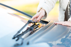 Hand picking up windscreen wiper. Woman's hand picking up windscreen wiper Royalty Free Stock Photography