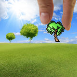 Hand picks pixel tree icon. Close up of hand picks pixel tree icon as concept Stock Photography