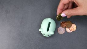 Hand with piggy bank and coins