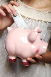 Hand and piggybank Stock Image
