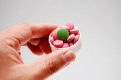 Hand with pill. A hand with several colorful pills Royalty Free Stock Images