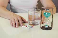 Hand with pill, water and glass of water. Person holding pill,clock and glass of water Royalty Free Stock Images
