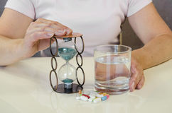 Hand with pill, water and glass of water. Person holding pill,sandglass and glass of water Royalty Free Stock Image