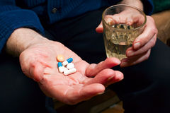 Hand With Pills. Close-up old man's hands with pills and glass of water, he is going to take some medicine Stock Images