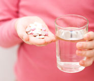 Hand with pills and glass of water Royalty Free Stock Images