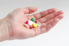 Hand with pills. Hand of woman holds multicolored pills on the light background Royalty Free Stock Images