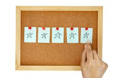 Hand pin note paper on cork pin board with give five star hand drawing , symbol of excellent customer satisfaction feedback. Hand pin a note paper on cork pin stock images