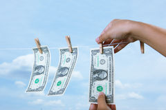 Hand pinch money on clothes line Royalty Free Stock Photo