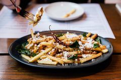 Hand pinching French fries with fried basil, Thai chili and feta cheese with fork. Thai fusion food.  royalty free stock image