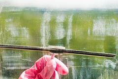 Hand in pink glove cleans window glass by squeegee Royalty Free Stock Photo