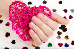 Hand with pink matte manicured nails holding a heart Royalty Free Stock Image
