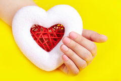 Hand with pink matte manicured nails holding a heart Royalty Free Stock Images