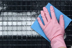 Hand in a pink rubber glove. A blue napkin wipes out the black dirt Royalty Free Stock Photography