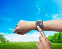 Hand plaatsende tijd op smartwatch Stock Foto