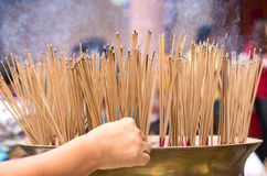 Hand places a stick of incense at a large pot. In Chinese temple Royalty Free Stock Photos