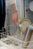 Hand places wine glass in dishwasher. Woman's hand places wine glass in dishwasher Royalty Free Stock Photo