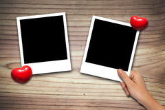 Hand placing Blank valentine photo frames Stock Photography