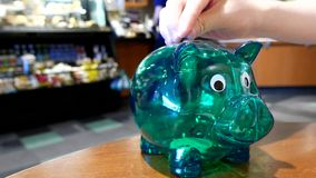 Hand placing coins on green piggy bank stock footage
