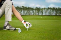 Hand placing golf ball on tee Royalty Free Stock Photo