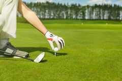 Hand placing golf ball on tee Royalty Free Stock Photo