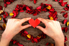 Hand placing heart in centre of red potpourri heart Stock Photo