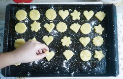 Hand placing a heart shaped cookie on a tray royalty free stock photography