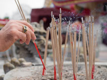 Hand placing incense into an incense pot Royalty Free Stock Images