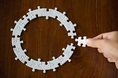 Hand placing the last jigsaw puzzle piece,conceptual of problem solving.  royalty free stock photography