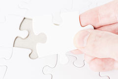 Hand placing the last puzzle piece Stock Image