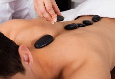 Hand placing lastone on man's back in spa Royalty Free Stock Images