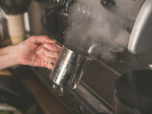 Hand placing metal cup under coffee machine tap Stock Photography