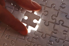 Hand placing missing puzzle piece Royalty Free Stock Photos