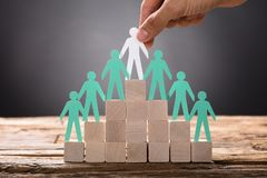 Hand Placing Paper Businessman With Employees On Pyramid Blocks. Closeup of hand placing paper businessman with employees on pyramid blocks stock photography