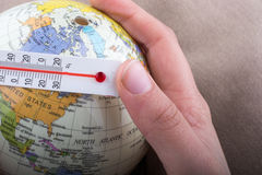 Hand placing a thermometer on a model globe Stock Images