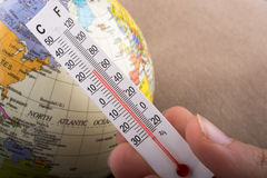 Hand placing a thermometer on a model globe Stock Photos